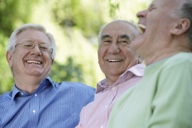Three senior men laughing, close-up (focus on man wearing glasses)