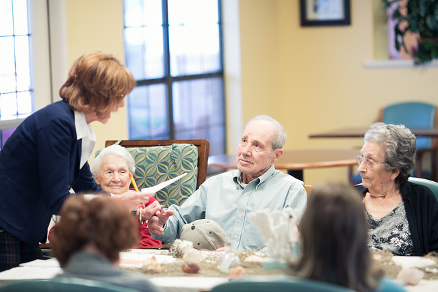 <Meyer leads a group of assisted living residents in a poetry session.