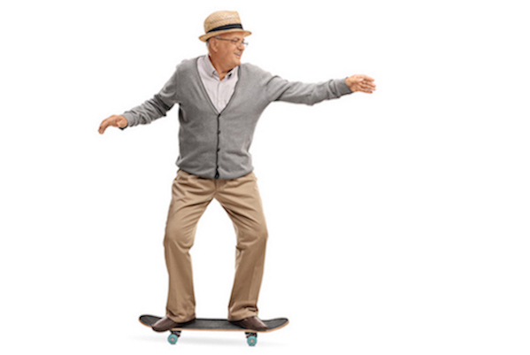 Joyful senior man riding a skateboard