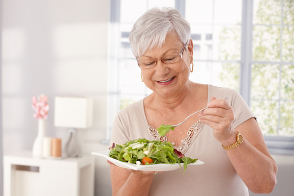 Old lady eating green salad