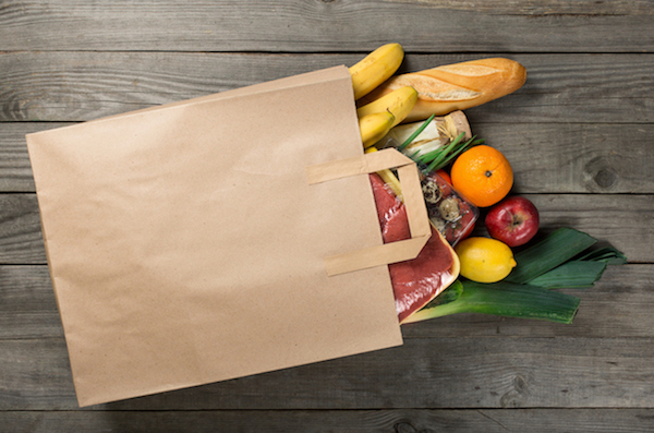 Different food in paper bag on wooden background, close up