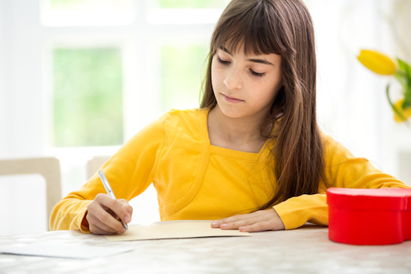 adorable girl writing greeting card