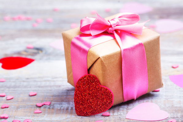Gift box with pink bow ribbon and glitter hearts on wooden rustic background