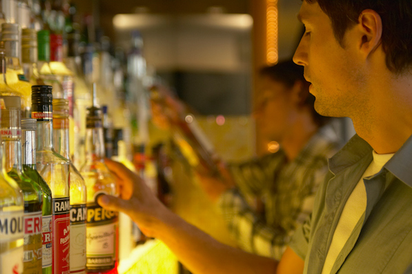 """Bartender reaching for bottle of spirits, close-up"""