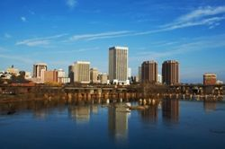 The skyline of Richmond, VA (Virginia) is seen reflected in a nearby river