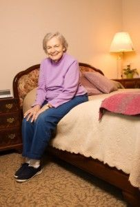 Elderly Caucasian woman in bedroom.