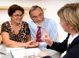 Hispanic couple discussing long-term insurance with their financial advisor