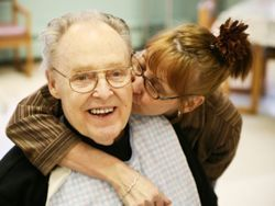 daughter kissing smiling old man at a nursing facility